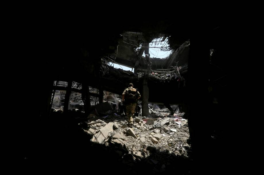 Membros da Divisão Especial de Emergência iraquiana andam sobre escombros de um prédio na Cidade Velha de Mossul, Iraque