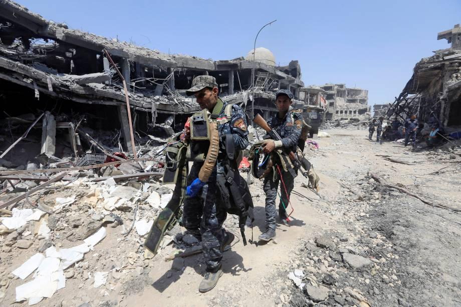 Membros da Polícia Federal iraquiana carregam cintos suicidas usados por militantes do Estados Islâmico, na Cidade Velha de Mossul, Iraque