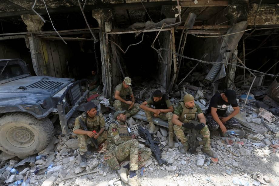 Membros da Divisão Especial de Emergência iraquiana descansam na Cidade Velha de Mossul, Iraque