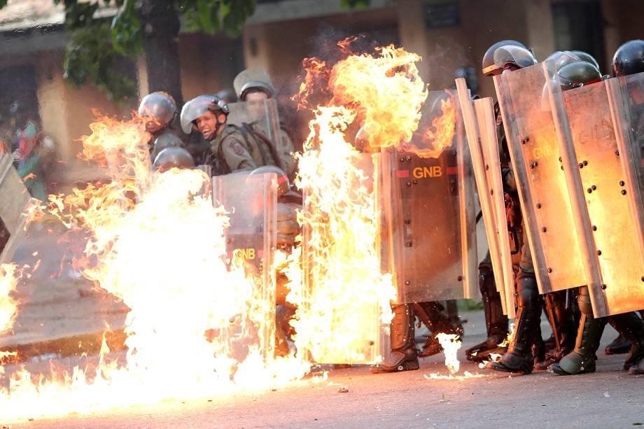Forças de segurança venezuelanas pegam fogo durante protesto contra o presidente Nicolás Maduro, em Caracas - 27/07/2017