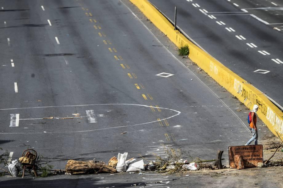 Manifestante da oposição venezuelana anda pela estrada Prado del Este, bloqueada durante a greve geral de 48 horas contra o presidente Nicolás Maduro - 27/07/2017
