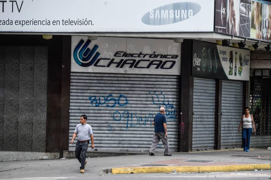 Pessoas passam em frente as lojas de portas fechadas devido à greve geral de 48 horas contra o presidente Maduro, em Caracas - 27/07/2017