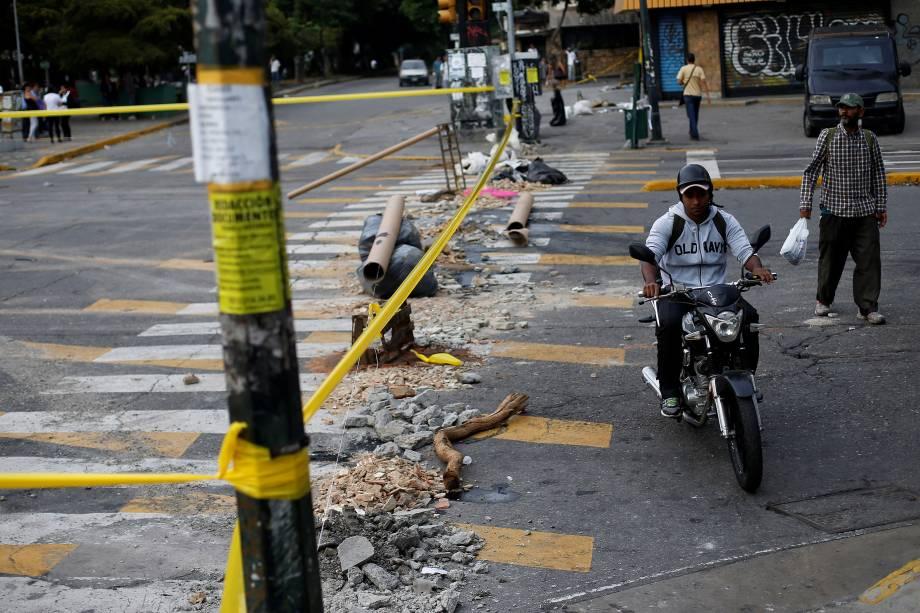 Motociclista passa em frente a uma rua bloqueada durante o segundo dia da greve de 48 horas organizada pela oposição venezuelana contra o presidente Nicolás Maduro, em Caracas - 27/07/2017