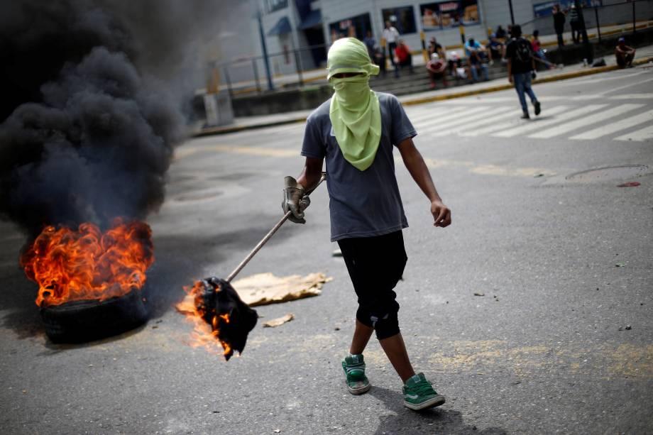 Manifestante da oposição venezuelana bloqueia uma rua durante a greve geral de 48 horas contra o presidente Nicolás Maduro, em Caracas - 27/07/2017