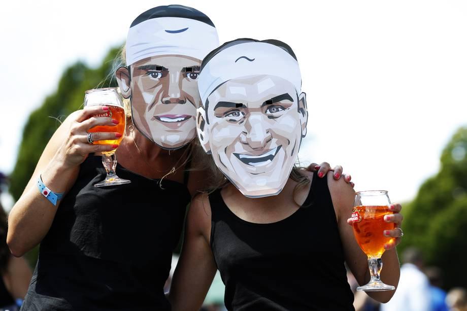Torcedoras usam máscaras dos tenistas Roger Federer e Rafael Nadal, em Wimbledon
