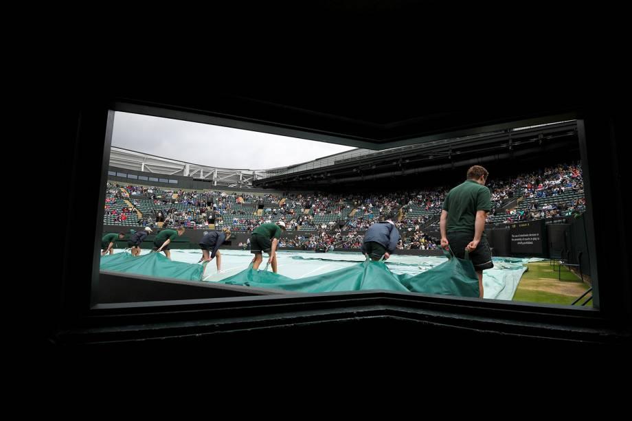 Assistentes cobrem quadra devido à chuva, em Wimbledon