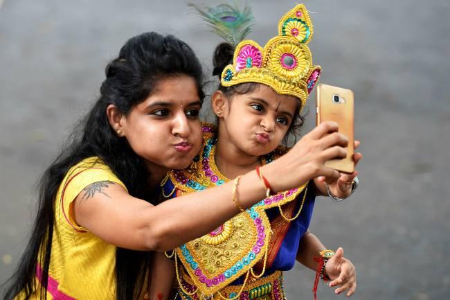 Indiana tira self com a filha, vestida como uma divindade para o Festival Janmashtami.