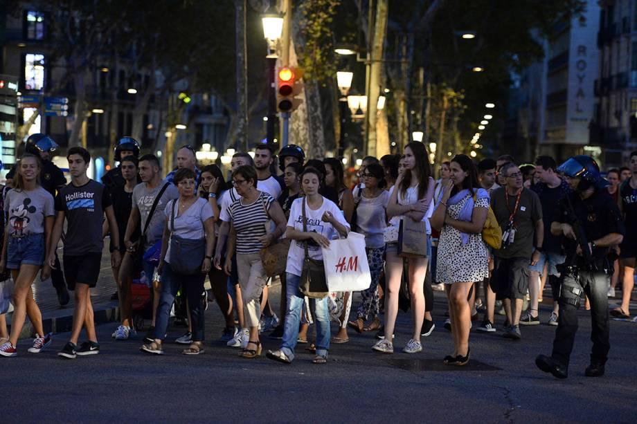 Policiais acompanham clientes de uma loja para fora da área isolada após atropelamento em La Rambla, em Barcelona