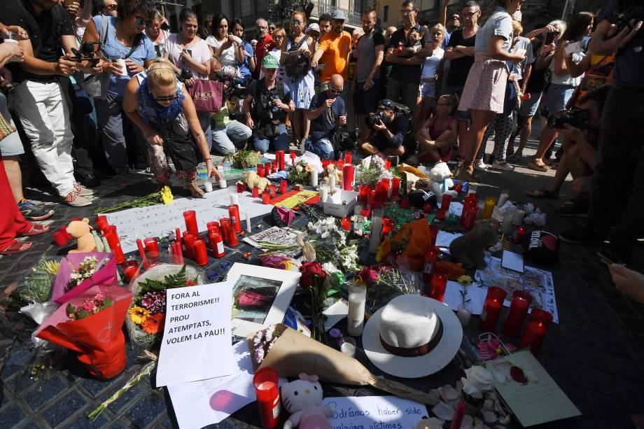 Pessoas levam flores, velas e cartazes para homenagear as vitimas do atropelamento terrorista em La Rambla, Barcelona, na Espanha