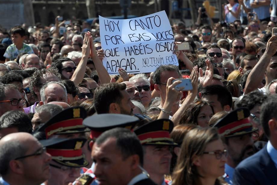 Cartaz com homenagem às vitimas do atentado terrorista em Barcelona é fotografado durante solenidade