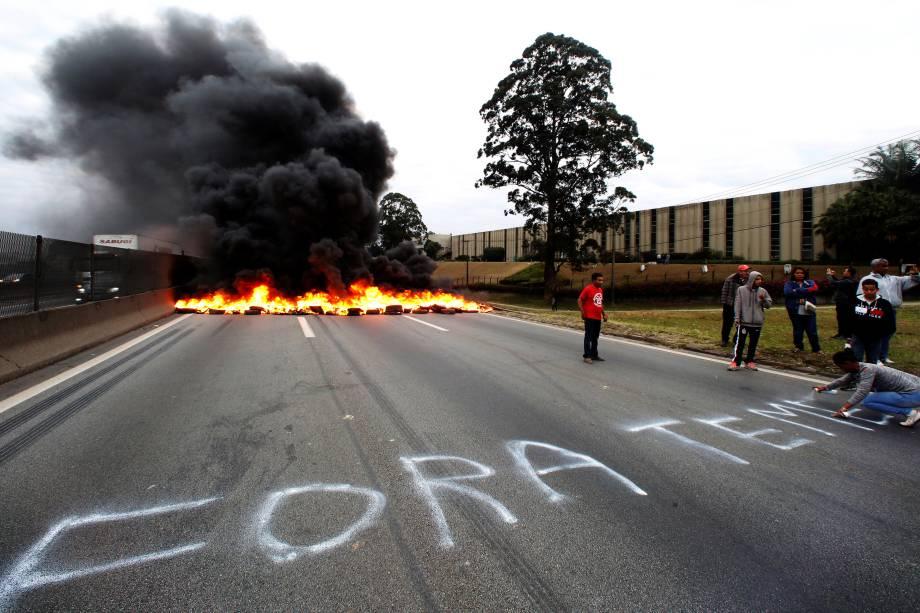Durante protesto contra Michel Temer na BR116, em São Paulo, membro do MTST pixa o asfalto pedindo a saída do presidente - 02/08/2017