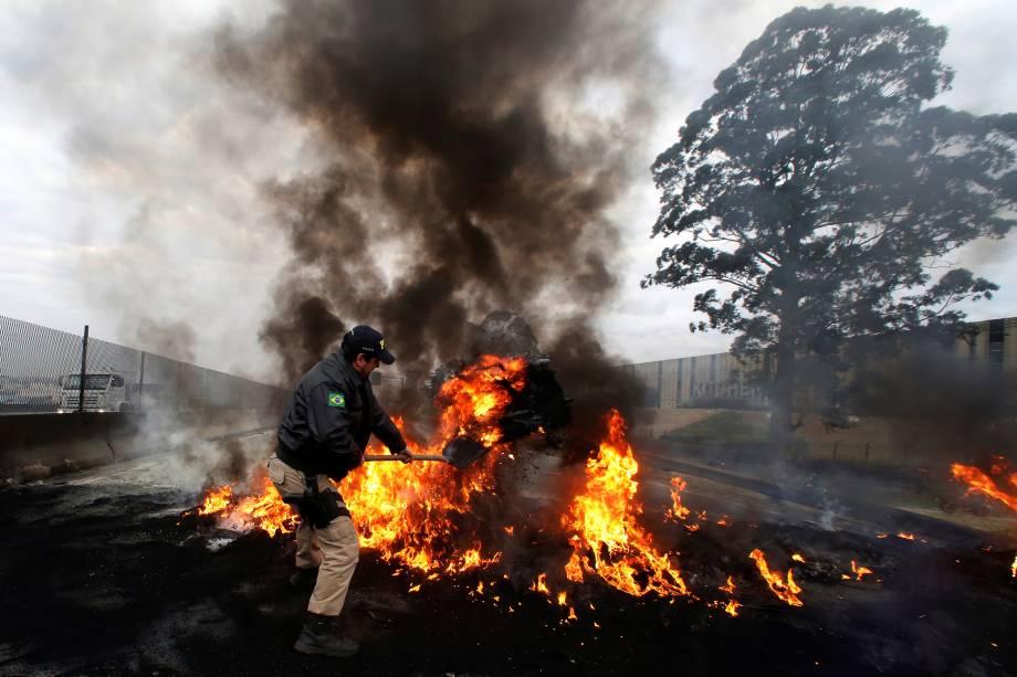 Policial Federal tenta desmanchar barricada feita pelos manifestantes do MTST durante protesto contra o presidente Temer na rodovia BR116, em São Paulo - 02/08/2017