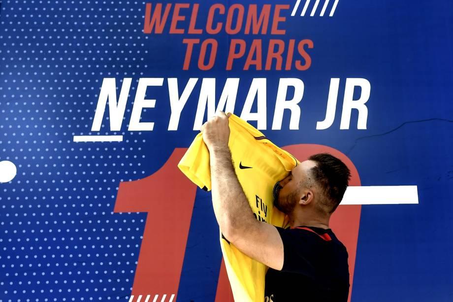 Torcedor beija a camisa recém adquirida de Neymar em frente à loja oficial do PSG em Paris
