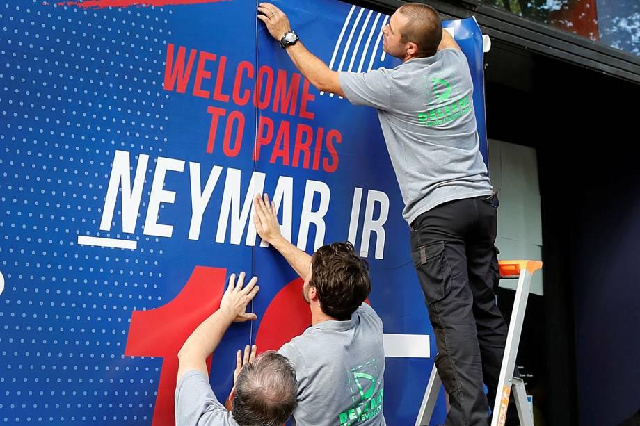 Funcionários de umaloja do PSG na avenida Champs Elysses, em Paris, preparam a fachada com boas-vindas à Neymar