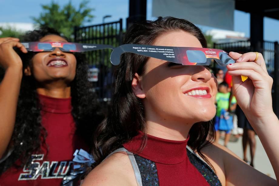 Animadoras de torcida usam óculos de visão solar antes de receber o público em um estádio de futebol-americano para assistir o eclipse solar total na Southern Illinois University em Carbondale, nos Estados Unidos - 21/08/2017