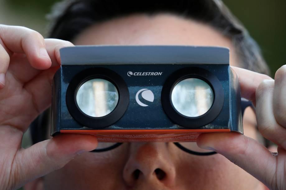 Homem olha através de um óculos especial o eclipse solar total em Nova York, nos Estados Unidos - 21/08/2017