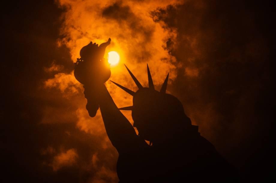 Eclipse solar é visto por trás da Estátua da Liberdade em Liberty Island, na cidade de Nova York - 21/08/2017