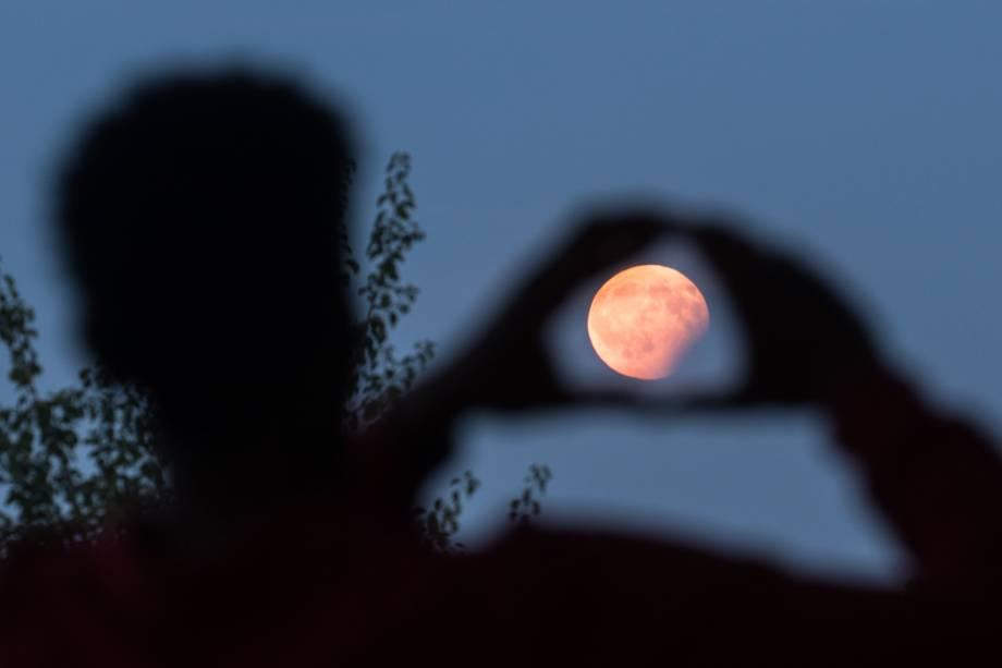Homem é fotografado encaixando a lua em sua mão durante o eclipse parcial em Frankfurt, na Alemanha - 07/08/2017