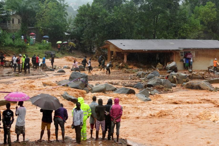 Pessoas observam a lama de um deslizamento de terra que atingiu a capital da África Ocidental, Serra Leoa. Pelo menos 312 pessoas foram mortas e mais de 2.000 perderam suas casas quando as grandes inundações atingiram a cidade de Freetown - 14/08/2017