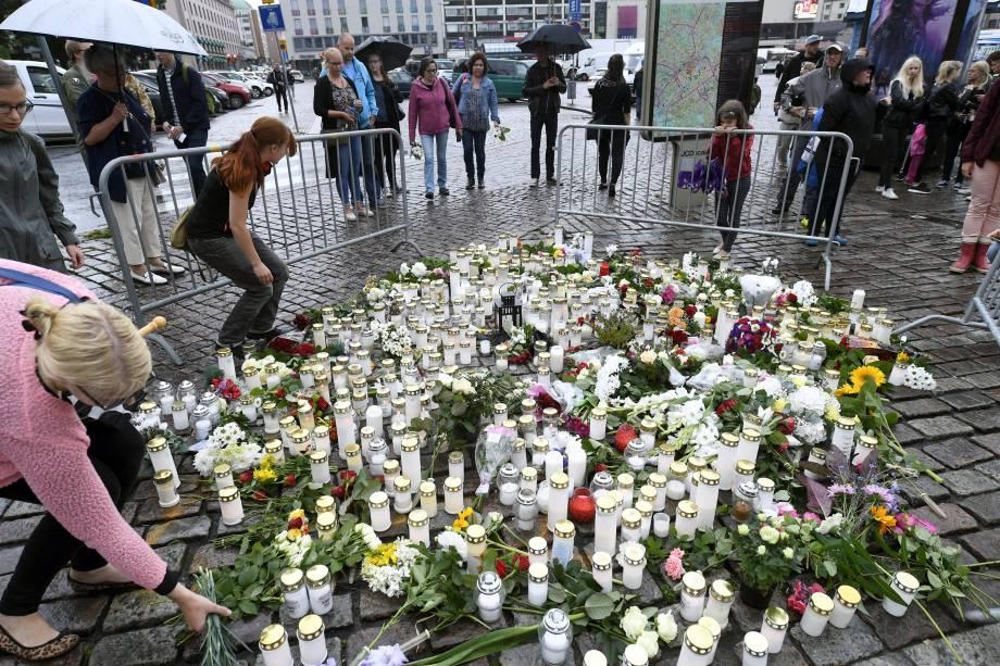 Pessoas levam velas e flores para um memorial improvisado em homenagem às vitimas esfaqueadas na Praça do Mercado, em Turku, na Finlândia