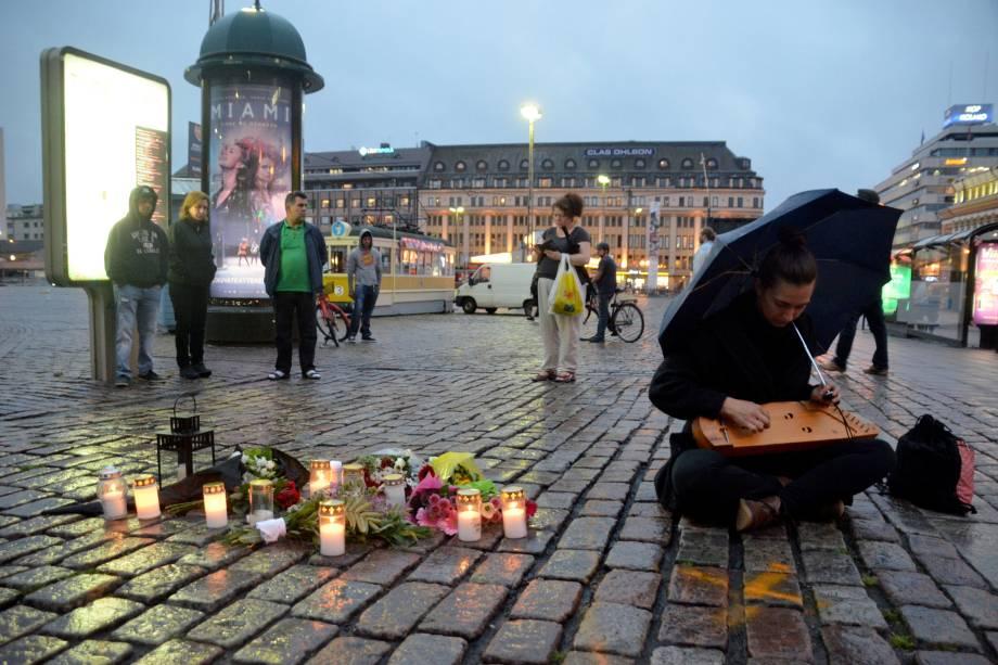 Mulher seu toca seu kântele, um instrumento tradicional da Finlândia, na Praça do Mercado, onde várias pessoas foram esfaqueadas durante um atentado, em Turku, na Finlândia