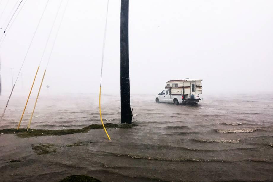 Carro passa por uma inundação na cidade de Corpus Christi, antes da chegada do furacão Harvey, no Texas