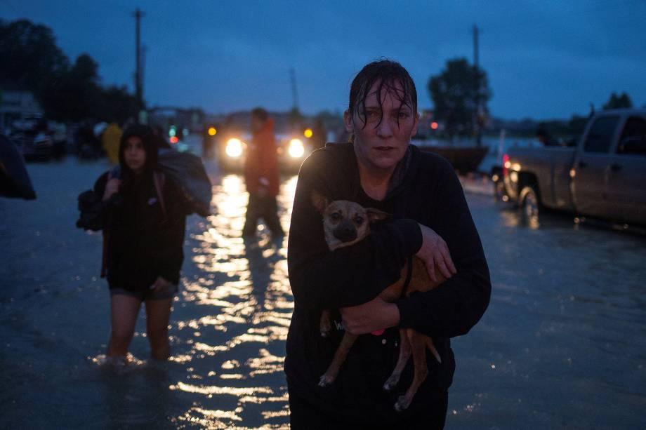 Uma mulher leva seu cachorro no colo durante a evacuação de casas em Houston, após a tempestade do furacão Harvey, no estado americano do Texas - 28/08/2017