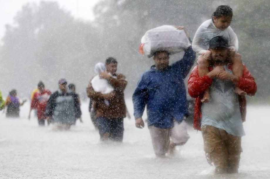 Moradores atravessam as águas da tempestade causado pelo furacão Harvey, em Beaumont Place, Houston, Texas, EUA - 28/08/2017