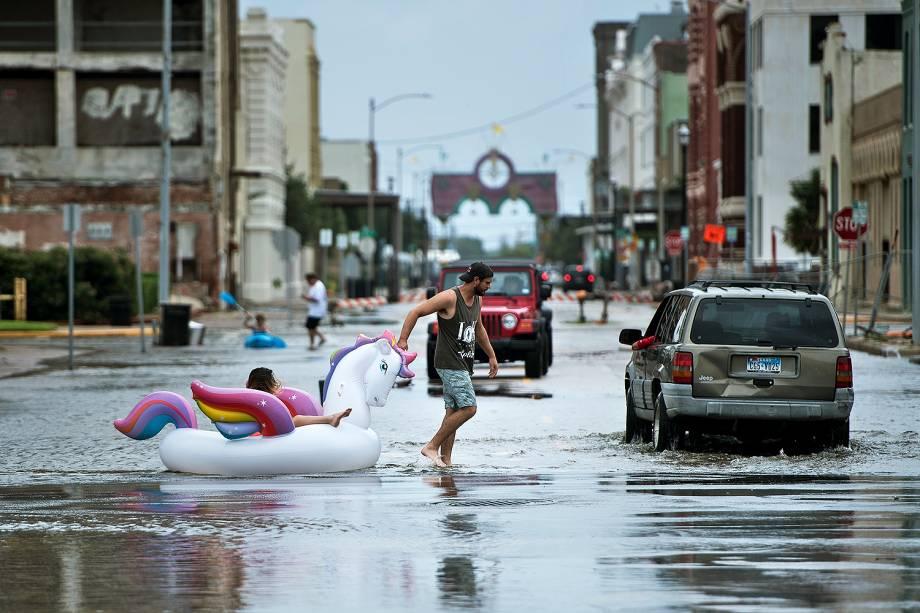 Pessoas caminham por uma rua inundada durante a passagem do furacão Harvey em Galveston, Texas - 27/08/2017