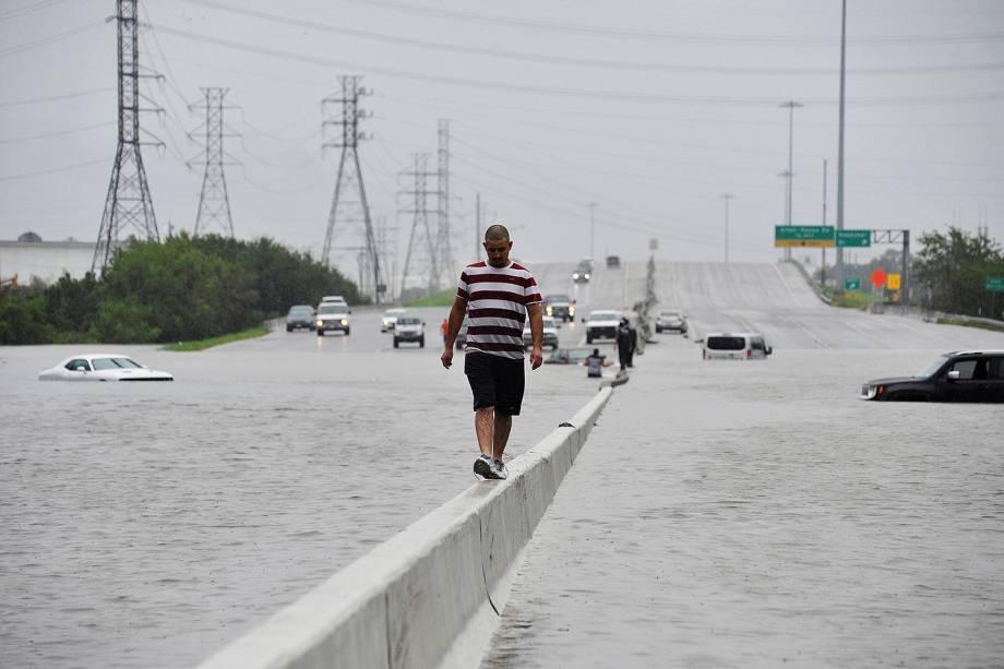 Pessoas caminham por uma rodovia inundada durante a passagem do furacão Harvey em Houston, Texas - 27/08/2017
