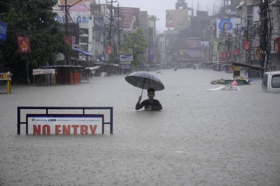 Homem percorre uma rua inundada durante um tempestade em Agartala, no estado indiano Tripura - 11/08/2017