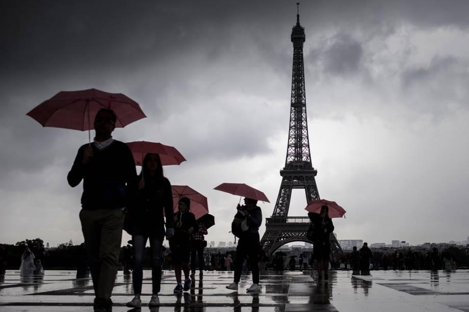 Pessoas andam com seus guardas-chuvas pelo pátio do Ancien Palais du Trocadéro, perto da Torre Eiffel, em Paris, na França - 10/08/2017