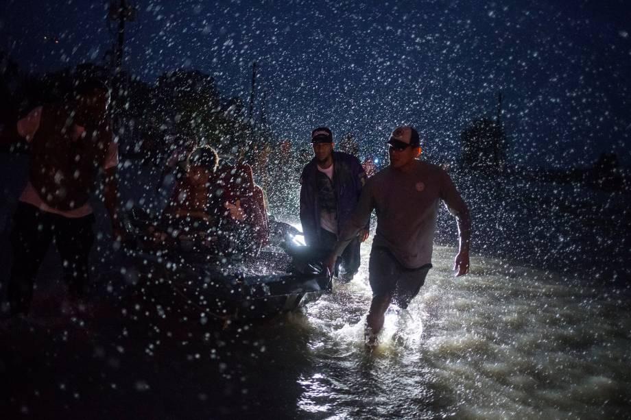 Voluntários ajudam a empurrar um barco com moradores retirados de suas residências durante inundação causada pela tempestade tropical Harvey em Houston, no Texas - 28/08/2017