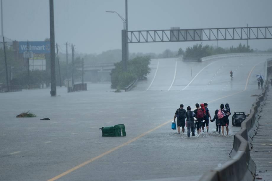 Moradores atravessam um viaduto com seus pertences após evacuarem suas casas em decorrências das inundações provocadas pela passagem do furacão Harvey em Houston, no estado americano do Texas - 27/08/2017