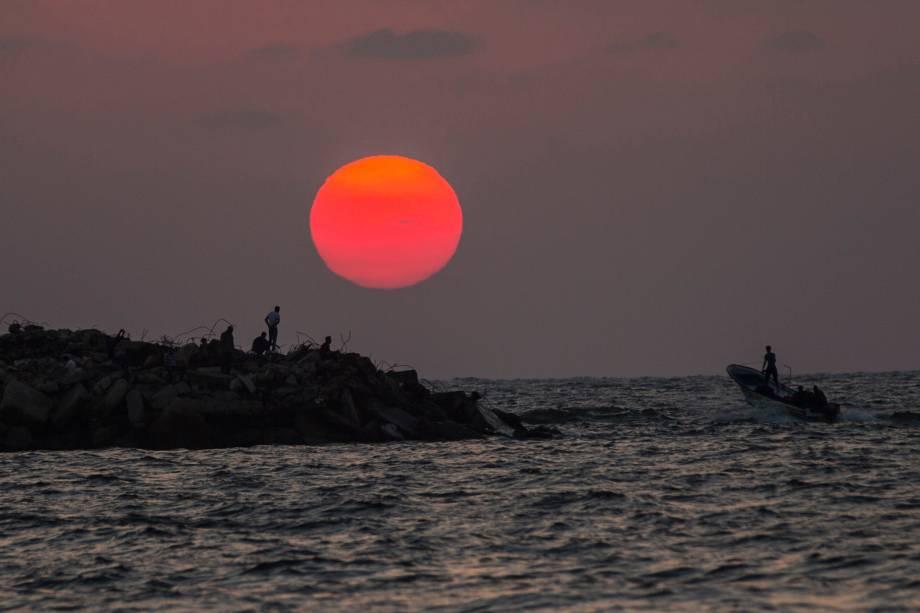 Um barco passa ao lado de uma costa rochosa onde palestinos observam o pôr do sol - 14/08/2017