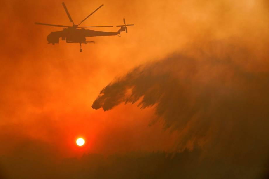 Um helicóptero do corpo de bombeiros despeja água para conter as chamas do incêndio florestal que atingiu a vila de Metochi, no norte de Atenas, Grécia - 15/08/2017