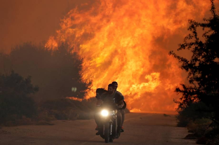 Homens fogem com um cão sobre uma moto de um incêndio florestal perto da vila de Varnavas, ao norte de Atenas, na Grécia - 14/08/2017