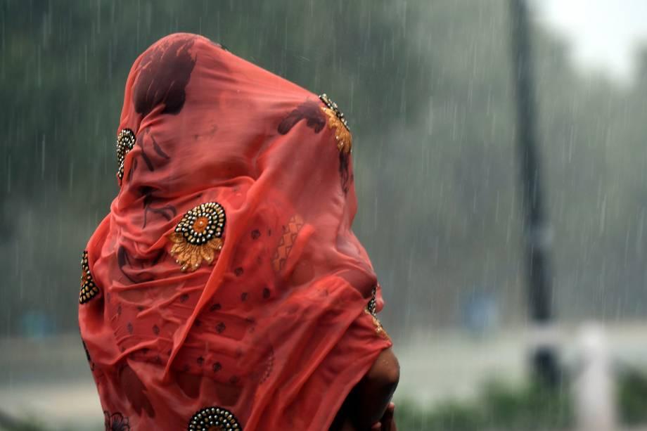 Mulher indiana cobre seu bebê com um pano vermelho durante uma forte chuva em Nova Deli - 07/08/2017