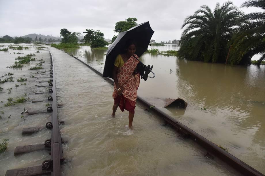 Mulher anda pelos trilhos do trem em Jakhalabandha afetada pela inundação em Koliabor, a cerca de 186 km de Guwahati no nordeste da Índia - 14/08/2017