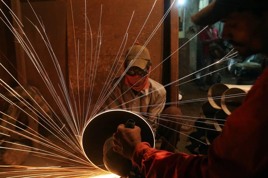 Trabalhadores usam uma serra elétrica para cortar canos em uma fábrica de tubos de metal, em Mumbai, na Índia - 11/08/2017