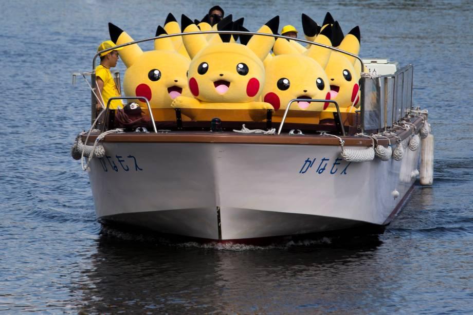 Artistas vestidos como Pikachu, personagem dos jogos e da série Pokémon, viajam em um barco durante o evento Pikachu Outbreak, organizado pelo The Pokemon Co. em Yokohama, na província de Kanagawa, Japão