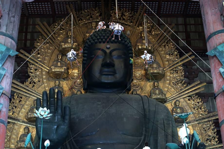 Monges budistas limpam a poeira da estátua do Grande Buda de 15 metros de altura no Templo de Todaiji, construída em 752 a.C.  em Nara, no Japão - 07/08/2017