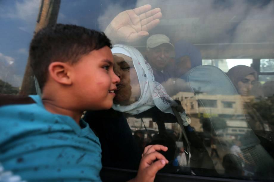 Uma mulher palestina beija seu neto pela janela de um ônibus enquanto se despede para a peregrinação anual de Hajj, na cidade de Khan Younis, sul da Faixa de Gaza - 14/08/2017