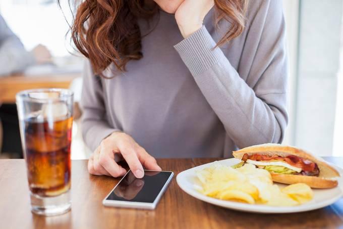 Mulher comendo e usando celular