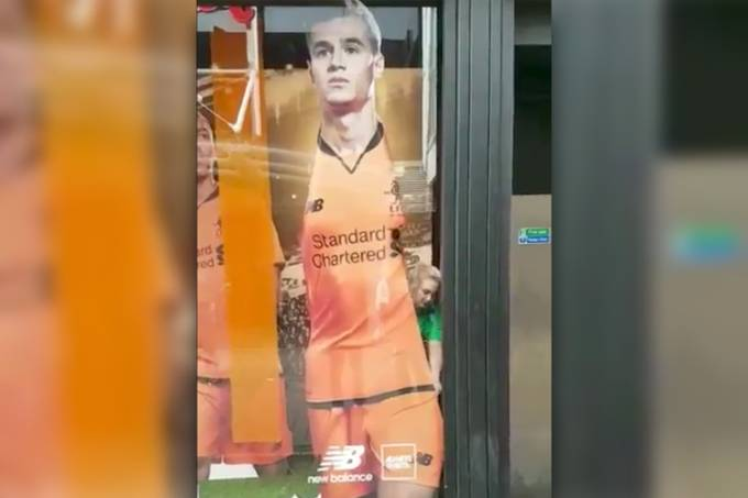 Funcionária retira imagem de Philippe Coutinho da loja do Liverpool