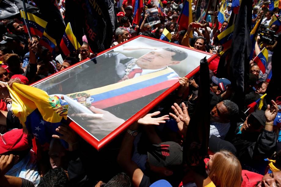 Partidários do ditador da Venezuela, Nicolás Maduro carregam um retrato de Hugo Chávez do lado de fora do Palácio Legislativo Federal durante a primeira sessão da Assembleia Nacional Constituinte, em Caracas - 04/08/2017
