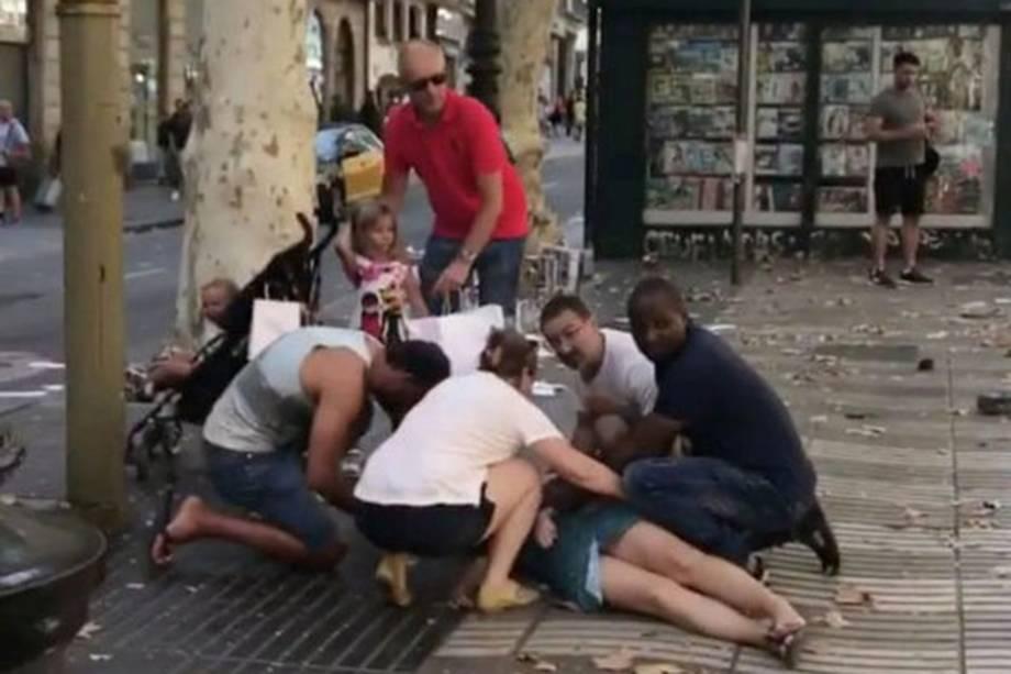 Pessoas ajudam uma mulher ferida depois de um atropelamento nos arredores da avenida Las Ramblas, no centro de Barcelona, na Espanha - 16/08/2017