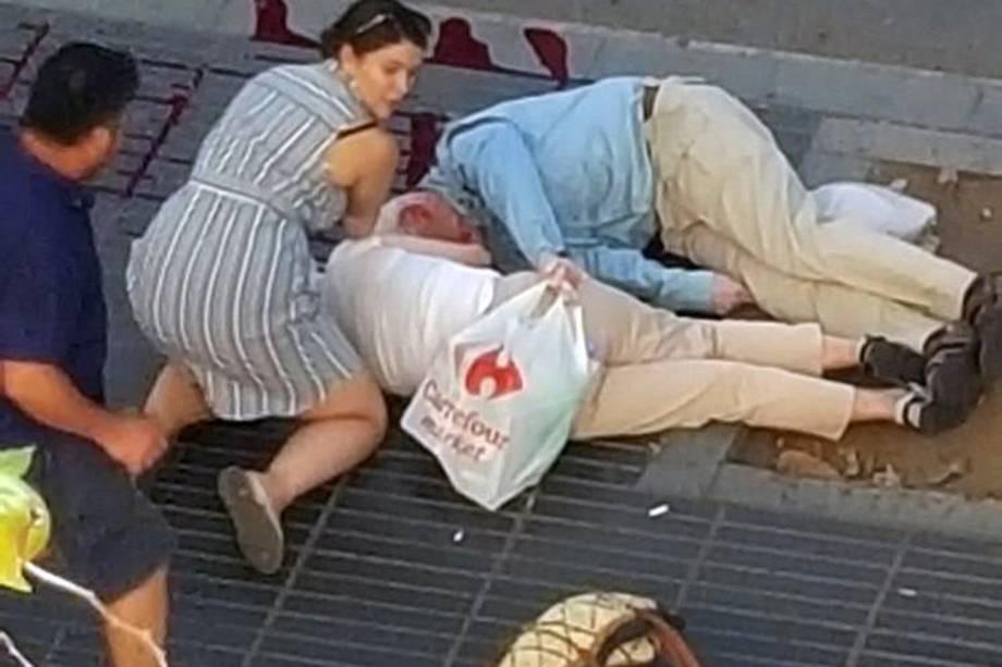 Mulher acode vítimas de atropelamento terrorista em La Rambla, Barcelona, na Espanha