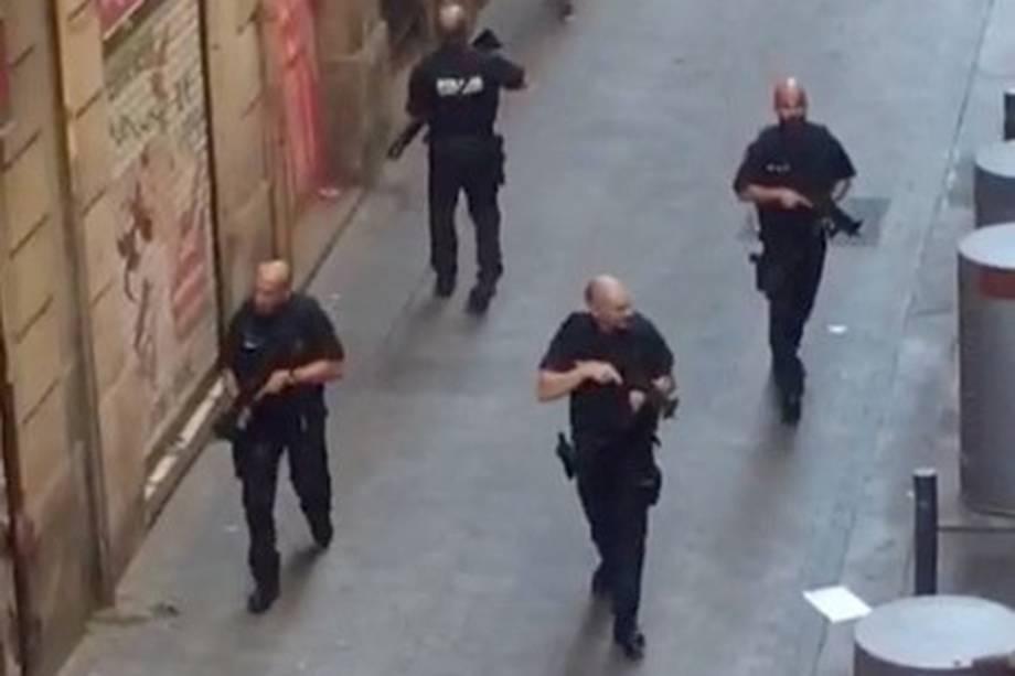 Policiais armados patrulham uma rua vazia, depois de uma van ter atropelado pedestres nos arredores da avenida Las Ramblas, no centro de Barcelona, na Espanha - 17/08/2017