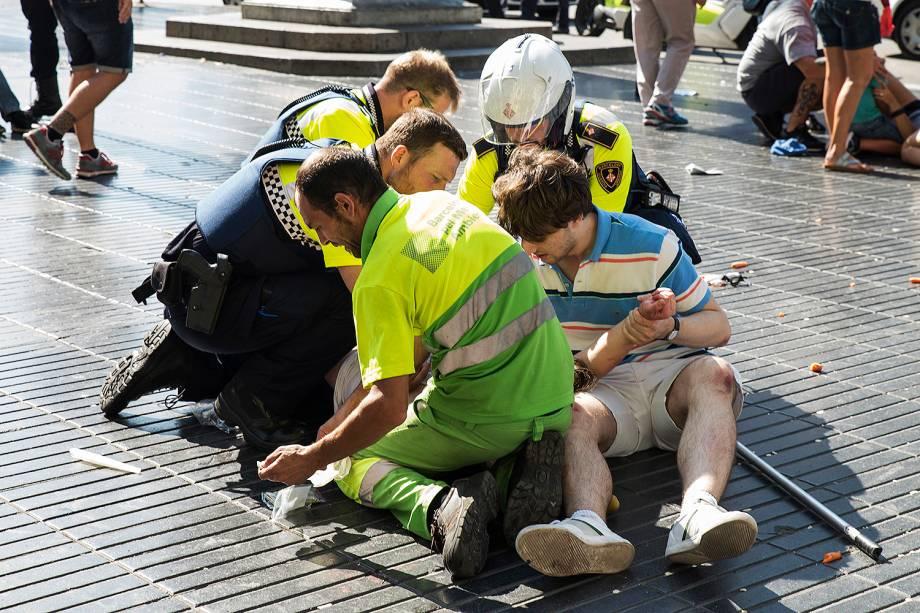Equipe de resgate ajuda uma mulher ferida depois de um atropelamento nos arredores da avenida Las Ramblas, no centro de Barcelona, na Espanha - 16/08/2017